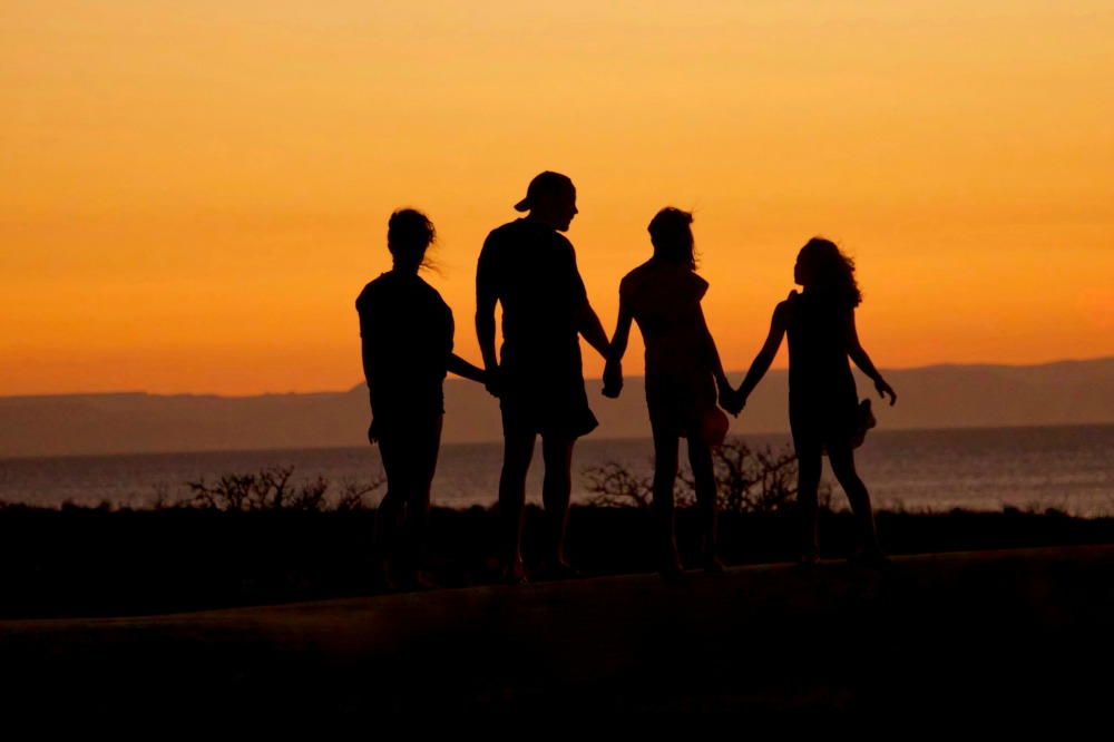 family holding hands at sunset mormon