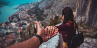 man holding wife's hand on mountainside