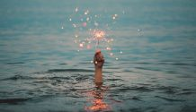 Hand holding sparkler above water.