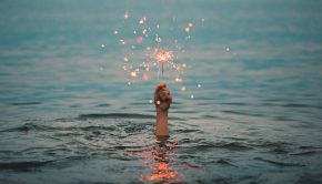 Hand holding sparkler above water.