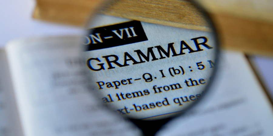 "A magnifying glass over the word ""Grammar."""