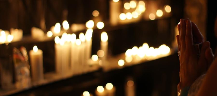 Hands praying near candles.