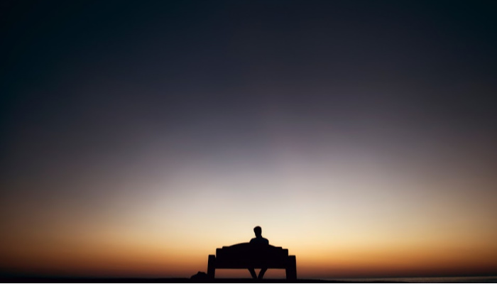 Silhouette of man sitting on bench.