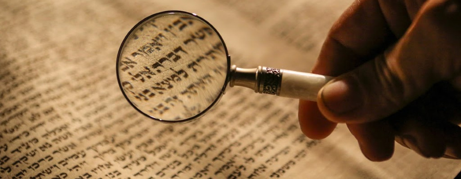 Man holding magnifying glass over Hebrew text.