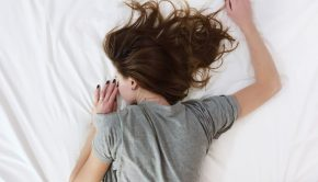 young woman lying on her stomach in bed
