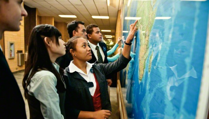 Group of lds missionaries pointing to wall map