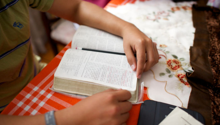 Young person's hands reading scriptures on a table