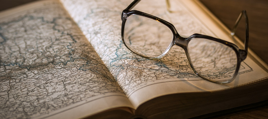 Glasses on an open book of maps.