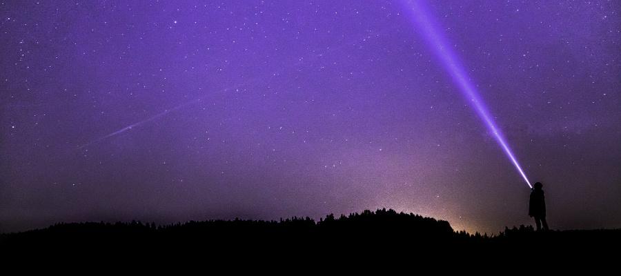 Mormon man shining flashlight in night sky.