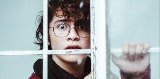 Man looking nervously through window.