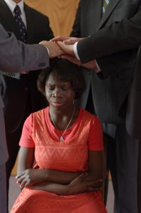Woman receiving a blessing.