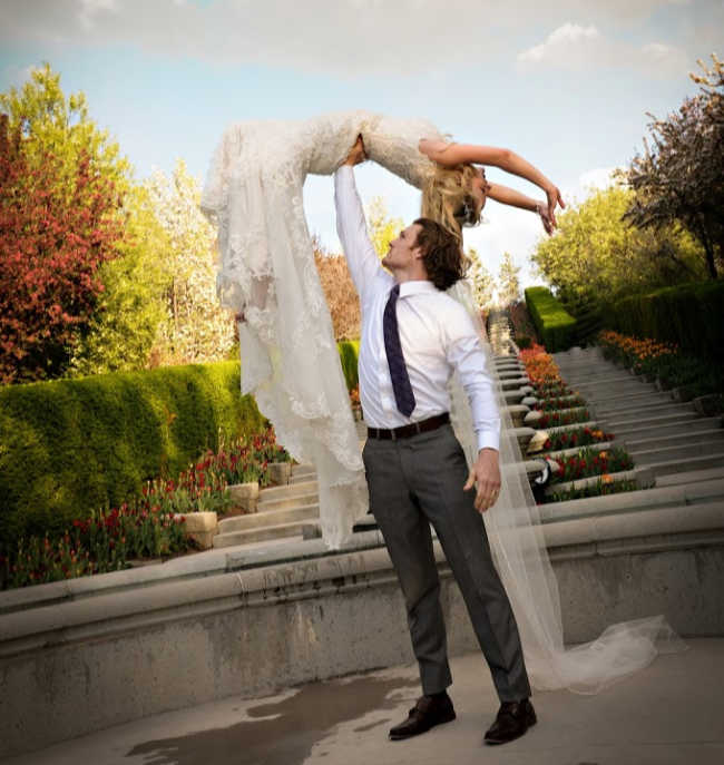 man lifting woman into air in a wedding dress
