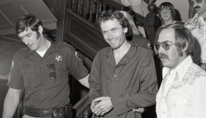 ted bundy being escorted by a police officer