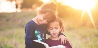 sister siblings hugging and reading scriptures out loud