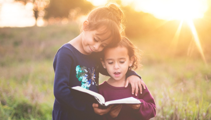 sister siblings hugging and reading scriptures out loud