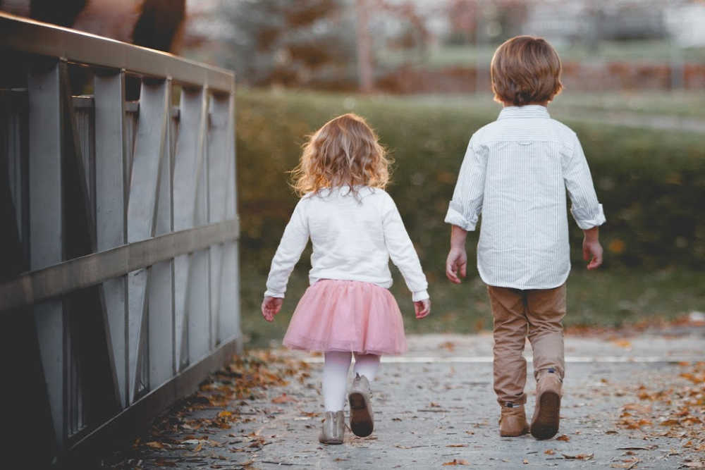 brother and sister sibling relationship walking on a bridge