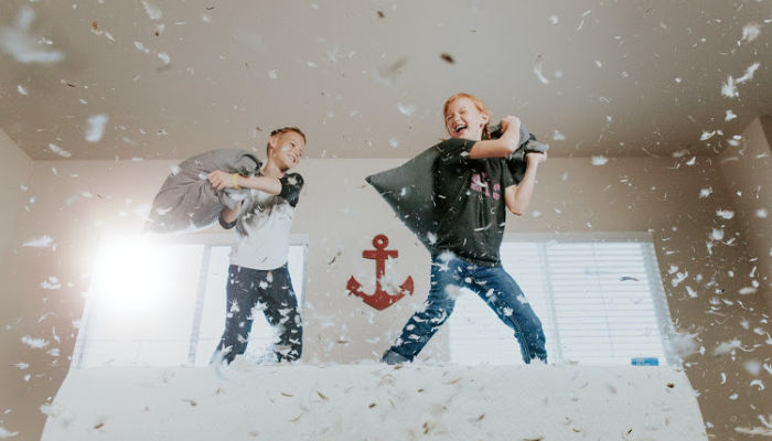 two kids pillow fighting with each other during covid-19