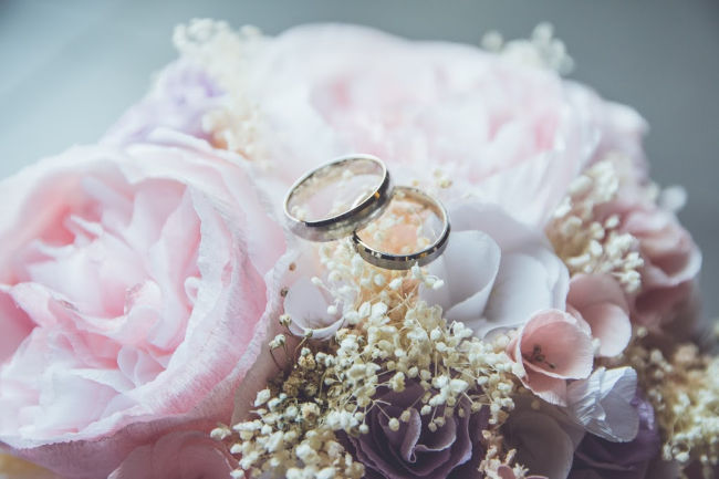 wedding rings sitting on flowers