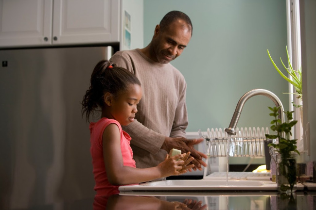 father and daughter washing their hands together at home