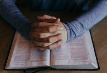 man's praying hands on scriptures