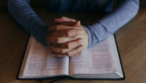 man's praying hands on scriptures