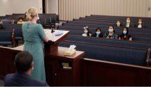 Woman speaking in Church while members practice social distancing.