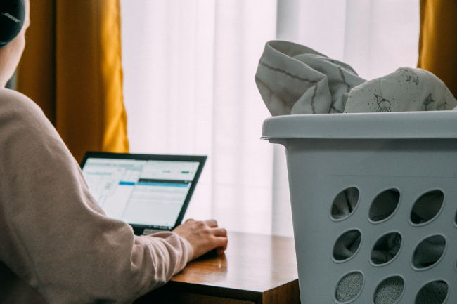 woman working from home with laundry next to her