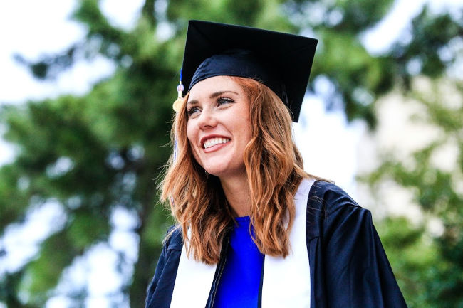 girl graduate wearing cap and gown smiling