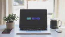 a laptop showing the words be kind