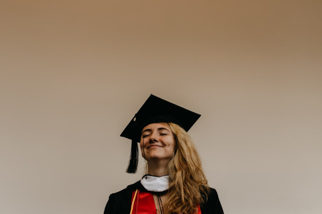 girl wearing cap and gown smiling