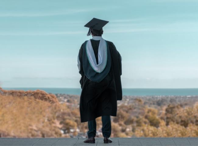 person in graduating cap and gown looking at a view
