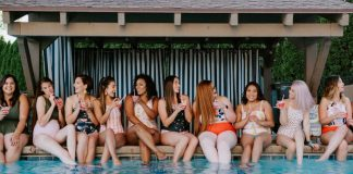 multiple women sitting by pool wearing modest swimsuits