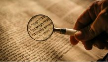 Magnifying glass over Hebrew text.