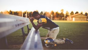 young man football player praying on sideline