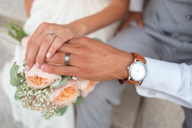 two hands wedding rings on flowers