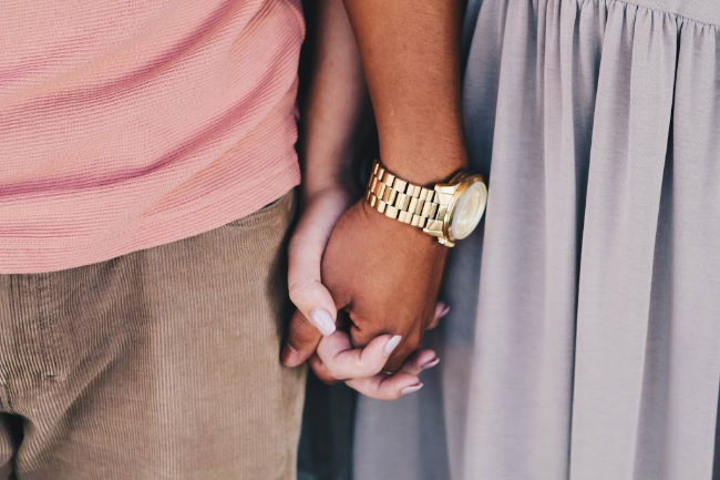 person of color holding a white persons hand