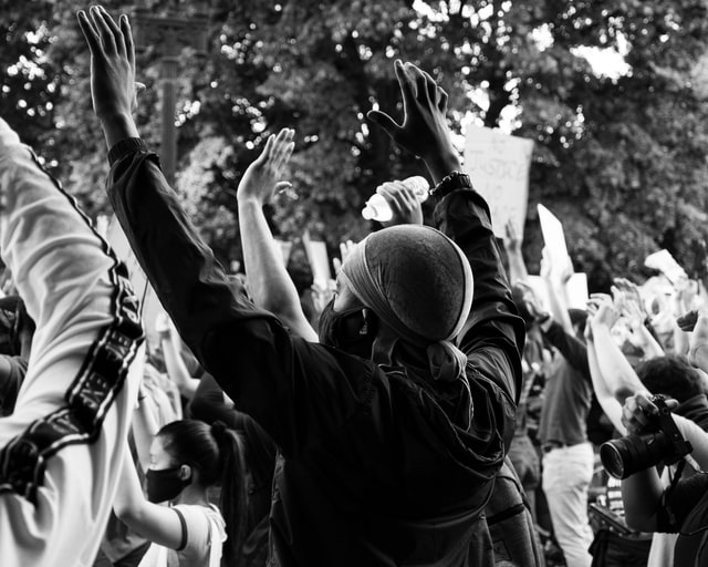 B&W of demonstrators with raised arms