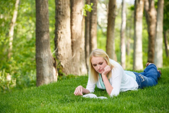 young woman laying on the grass reading the book of mormon
