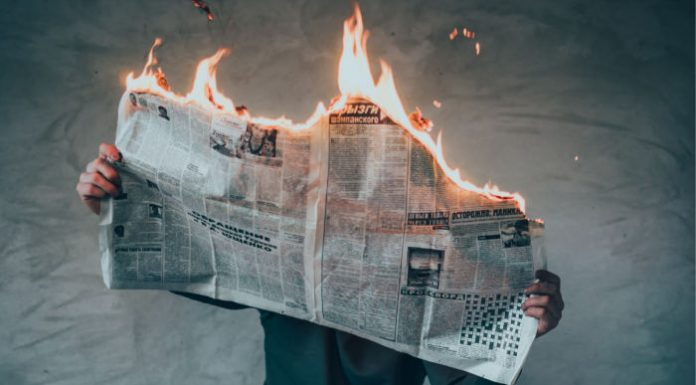 man holding a newspaper that is on fire