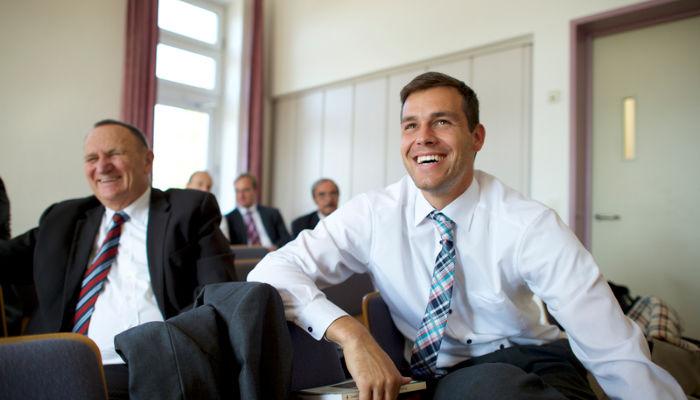 men sit together in elders quorum on sunday