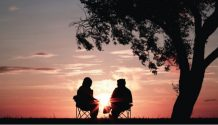 couple sitting together under tree talking