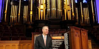 man sitting on organ at temple square for organ concert