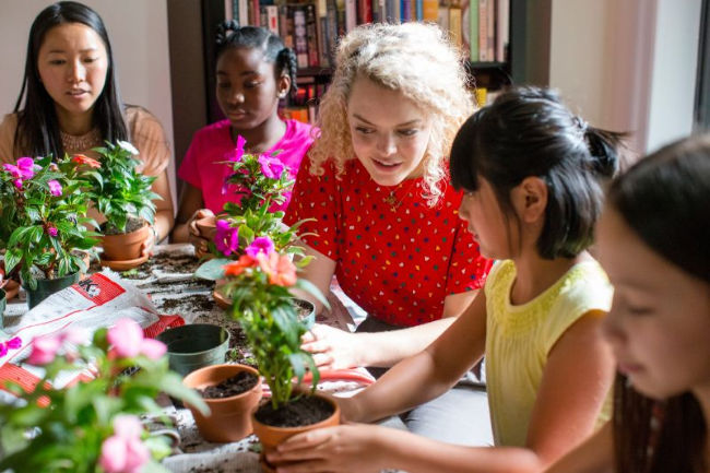young woman helps girls plant flowers for a church activity