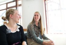 two sister missionaries laughing together sitting down