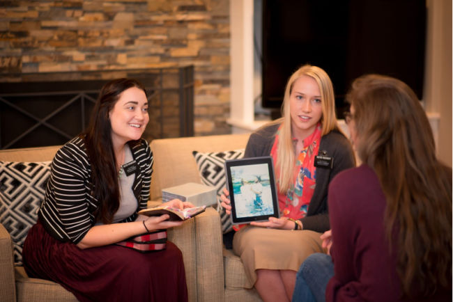 two sister missionaries holding tablet and teaching lesson