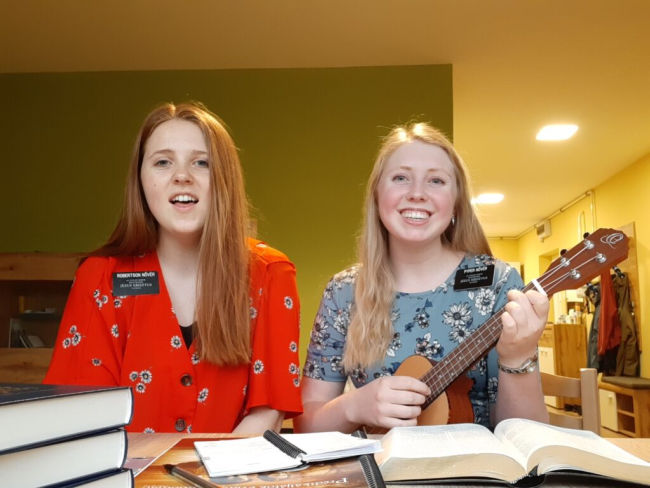 two sister missionaries at home doing livestream