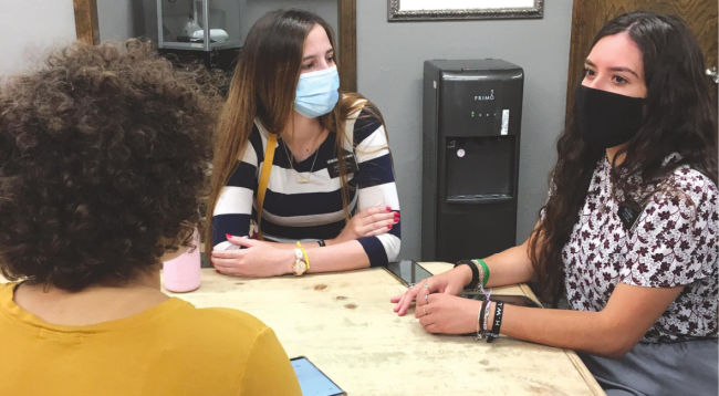 two sister missionaries teaching someone serving mission during COVID-19 wearing masks