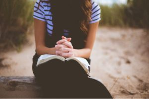girl praying with scriptures