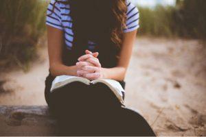 niña rezando con escrituras