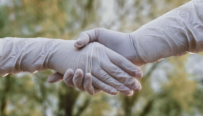 two people shaking hands wearing gloves during covid-19